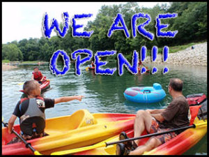 family kayaking with a sign saying we are open